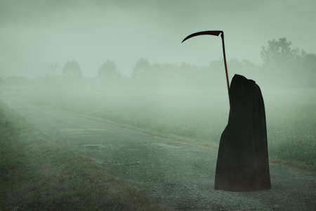 Hooded death with scythe waiting on a misty road . Halloween and horror Stock Photo