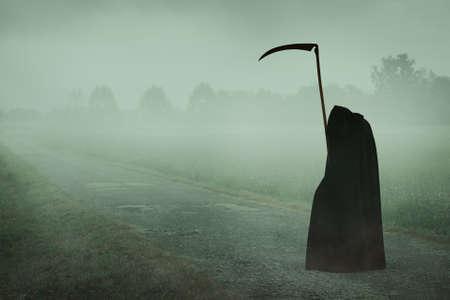 guadaña: la muerte con capucha con la guadaña de espera en un camino brumoso. Halloween y el horror