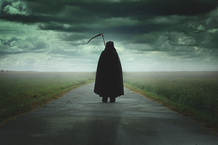 .Halloween과 죽음 어두운 황량한 도로에 산책하는 잔인 한 죽음의 사신