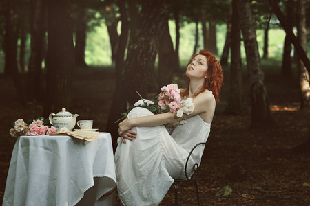 Beautiful red hair woman in a forest . Retro and surreal