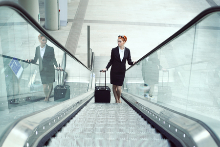arrival: Hostess on escalator in airport. Job and travel concept