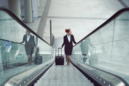 arrival: Businesswoman on escalator with baggage. Job and travel concept