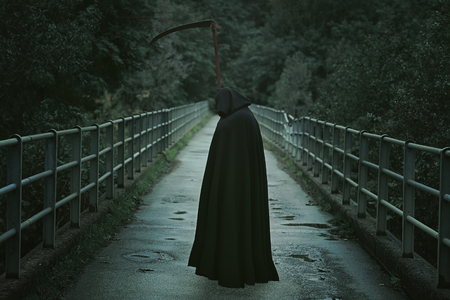 Grim Reaper: Hooded man with scythe waiting on a country bridge . Halloween and horror