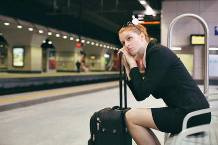 Bored businesswoman waiting train . Travel and stress