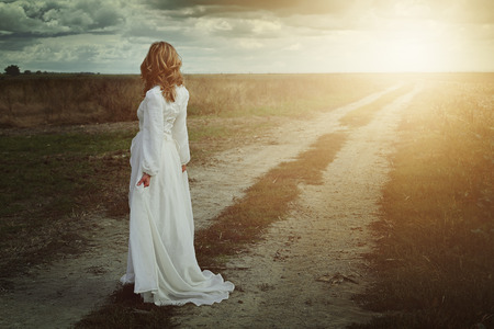 Woman in the fields looks sunset light. Romance and freedom 스톡 콘텐츠