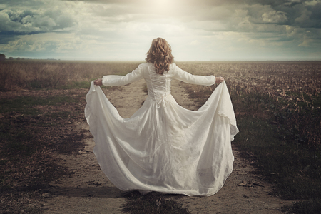 the innocence: Woman with beautiful dress in the country fields. Ethereal and innocence