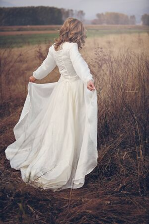 purity: Woman with vintage dress in dry fields. Romance and purity