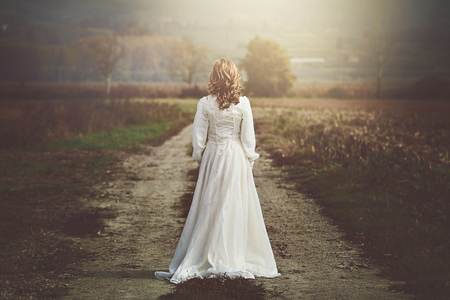 winter wedding: Bride with beautiful dress in country fields. Purity and innocence Stock Photo