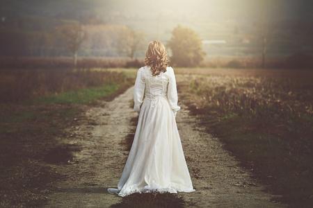 Novia con hermoso vestido en los campos del país. La pureza y la inocencia Foto de archivo - 47410703