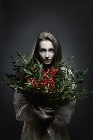 gothic woman: Dark portrait of a beautiful pale woman with bunch of red flowers . Vampire