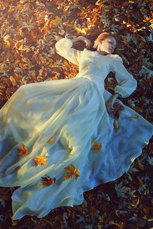 mysterious woman: Beautiful woman with victorian dress on a bed of leaves. Sadness and loneliness concept