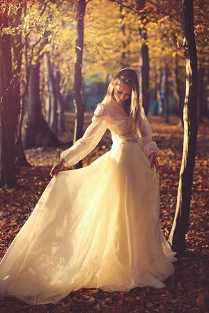 夕焼けの光の中のビクトリア朝のドレスの美女。秋の紅葉