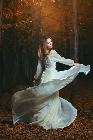 Beautiful woman dancing in dark autumn woods. Surreal and fantasy