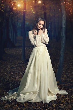 fairy forest: Beautiful victorian dressed woman in fairy forest. Romantic and fantasy