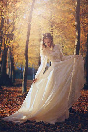 Beautiful woman with victorian dress in autumn woods . Sunset light