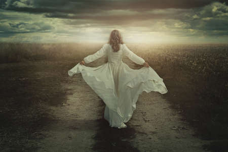 Woman running free in a desolate dark land. Surreal manipulation