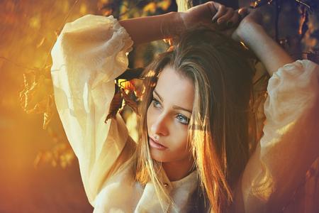 Autumn sunset light portrait of a beautiful woman . Seasonal colors