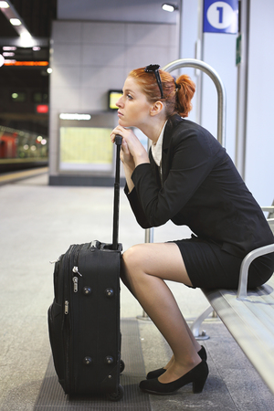 Businesswoman waiting train at subway station . Travel and stress