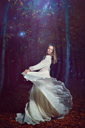 Beautiful woman dancing free with forest fairies . Surreal and fantasy