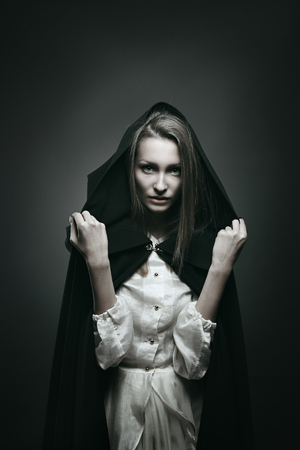 Dark portrait of a beautiful vampire with black hood . Halloween and horror concept