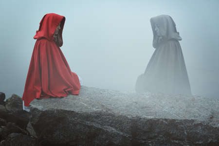 lost lake: Red hooded woman looks at her dark reflection in the fog . Surreal concept Stock Photo