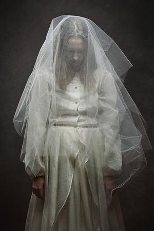 悲しい花嫁の暗いスタジオ撮影。ゴシックと超現実的