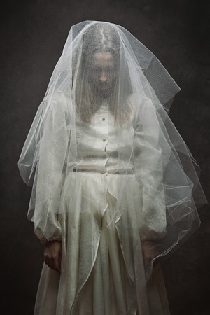 Dark studio shot of a sad bride . Gothic and surreal