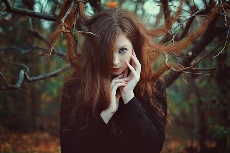 Outdoor portrait of red hair woman . Gothic and decadence colors