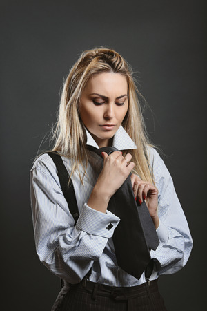 cufflinks: Beautiful woman with firm expression wearing a black tie. Business and fashion