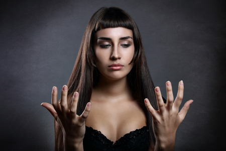 woman looking: Beautiful young woman looking at her hands with strange expression
