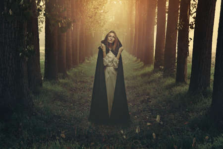Beautiful woman with black robe in a surreal forest