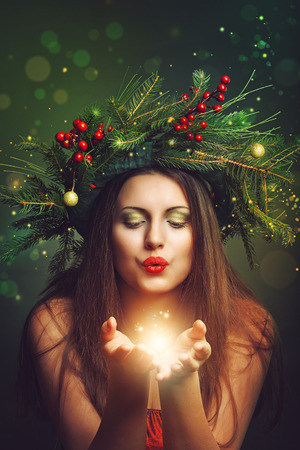 Beautiful woman blowing fairy and magical dust . Holiday and Christmas