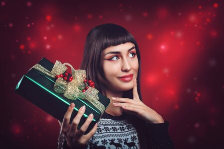 undecided: Beautiful woman with christmas package and undecided expression