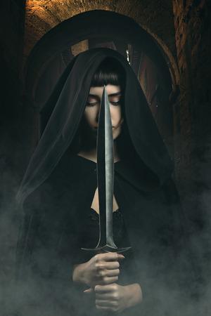 dark alley: Black hooded thief with knife in dark village alley . Fantasy and legend