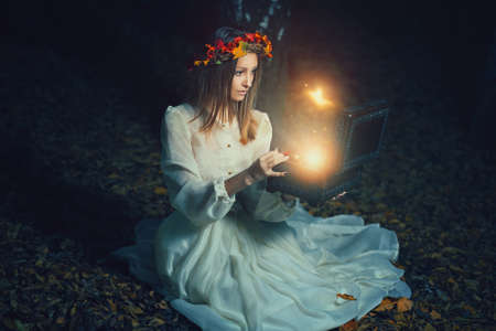 Beautiful woman opens a magical box full of fairies . Fantasy concept