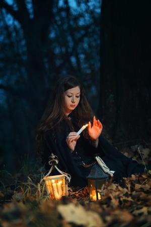 candela: Bella donna capelli rossi illuminata da una candela in una fantasia forest.Dark