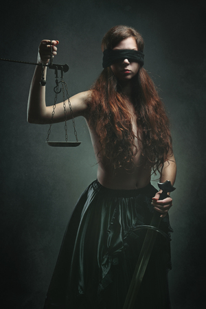 blindfolded: Portrait of a dark justice goddess with sword and scales. Mythology and fantasy