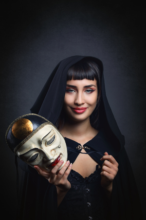 takes: Beautiful woman takes off the mask . Venetian carnival and party Stock Photo