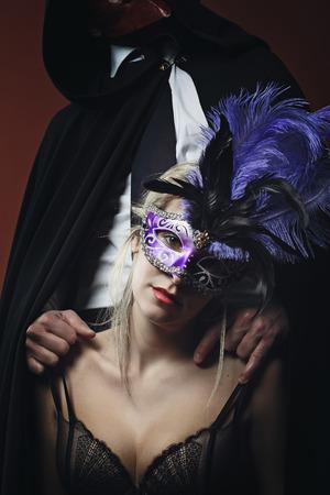 sexual intimacy: Mysterious woman in lingerie wearing venetian mask  . Dark seduction
