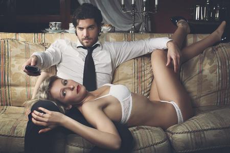 mujer elegante: Hermosa pareja viendo la televisión. Mujer en ropa interior