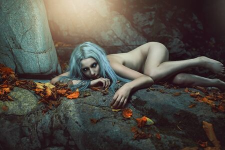 Dark daughter of the forest resting on rocks. Fantasy and myth