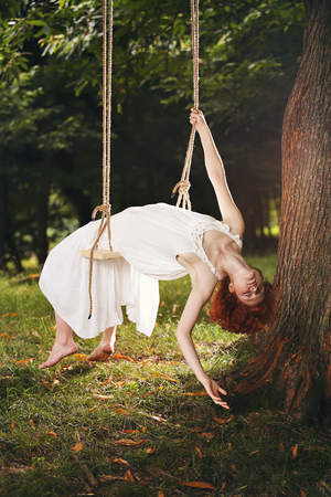 wood nymph: Beautiful woman bowing on a swing. Romantic and vintage portrait