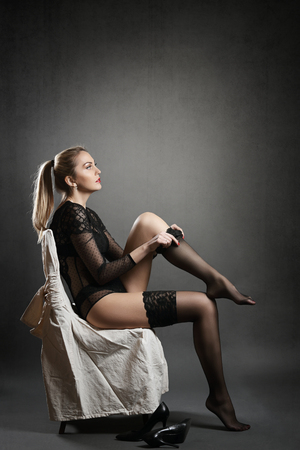 Beautiful woman dressing stockings. Grey background