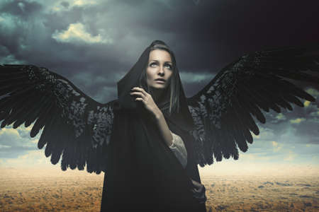 Fallen angel in a desert and stormy landscape. Fantasy and surreal Stock Photo