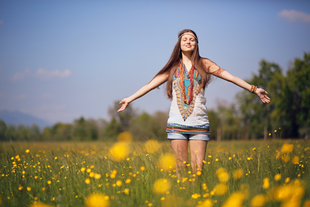 Free and smiling hippie in summer meadow. Vintage photo effect