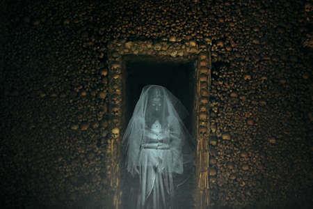 ghoul: Frightening ghost in a catacomb full of bones and skulls. Horror and halloween