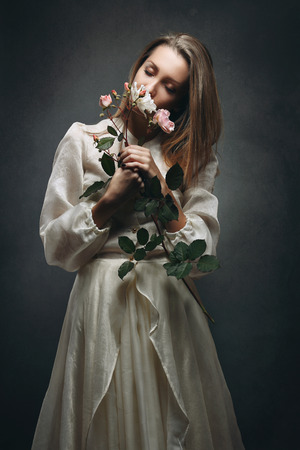 purity: Beautiful woman with victorian dress smelling flowers fragrance . Purity concept