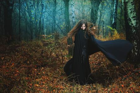 Mysterieuze vrouw wandelen in magisch bos. Fantasy en gothic Stockfoto