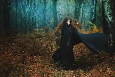 Mysterious woman walking in magical forest. Fantasy and gothic