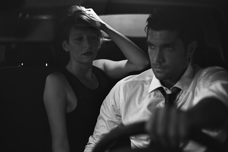 Seductive woman and driver on a car . Noir atmosphere